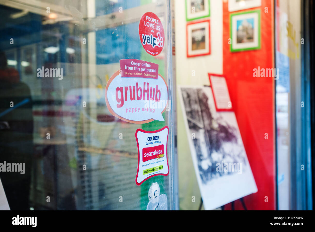 Stickers for seamless and grubhub internet food delivery services are seen on the window of a restaurant in new york