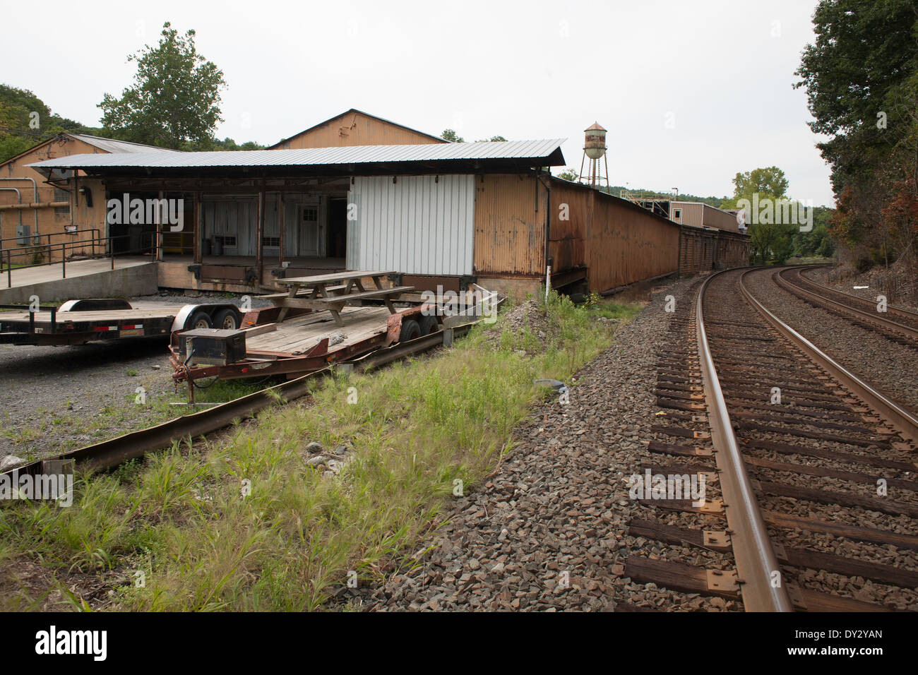Railroad tracks swing past an aging manufacturing building in Chatham in upstate New York. - Stock Image