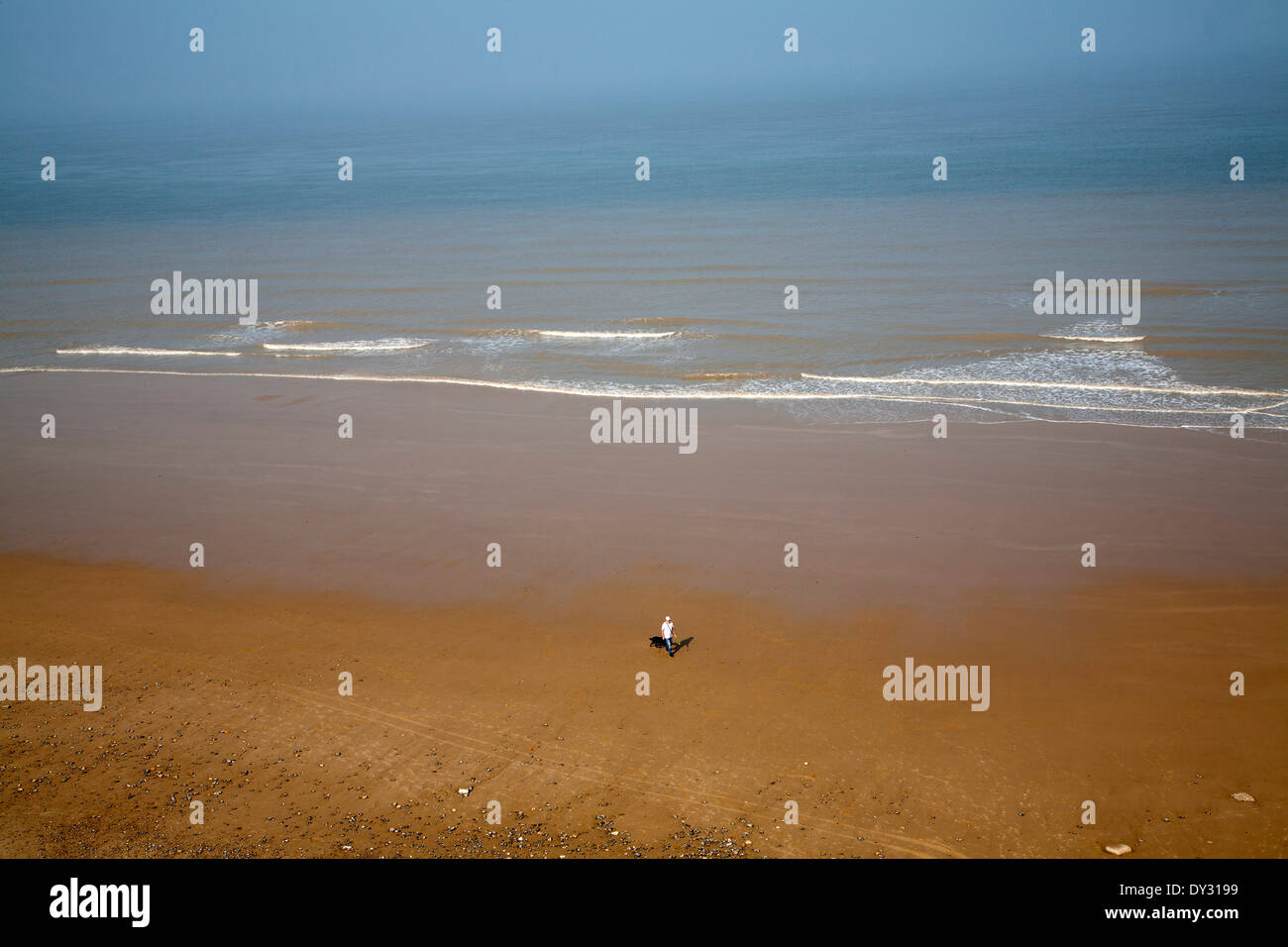 Overhead oblique view of a man walking across wide sandy beach at low tide, Overstrand, Norfolk, England - Stock Image
