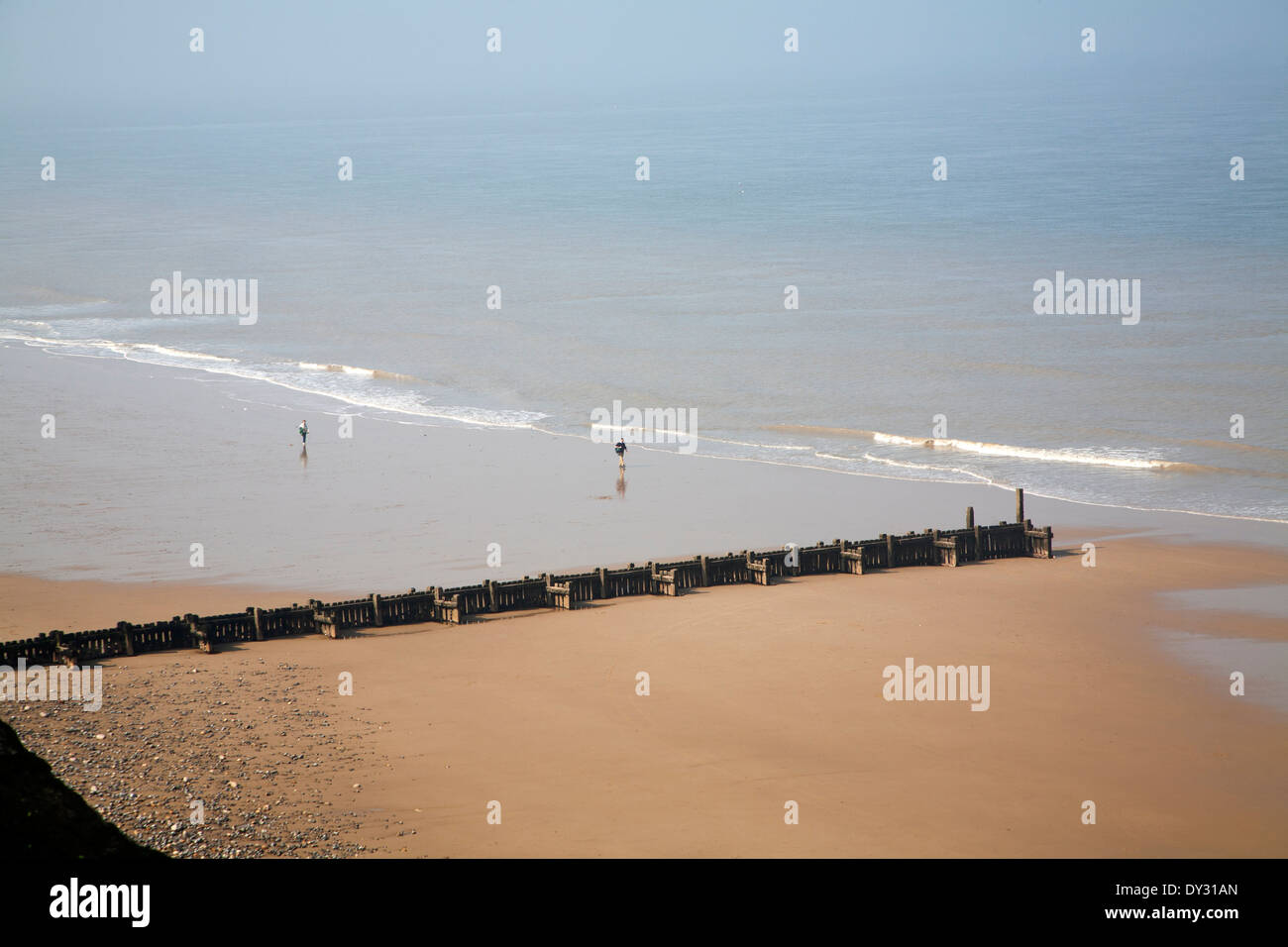 Overhead oblique view of two people walking across wide sandy beach at low tide, Overstrand, Norfolk, England - Stock Image