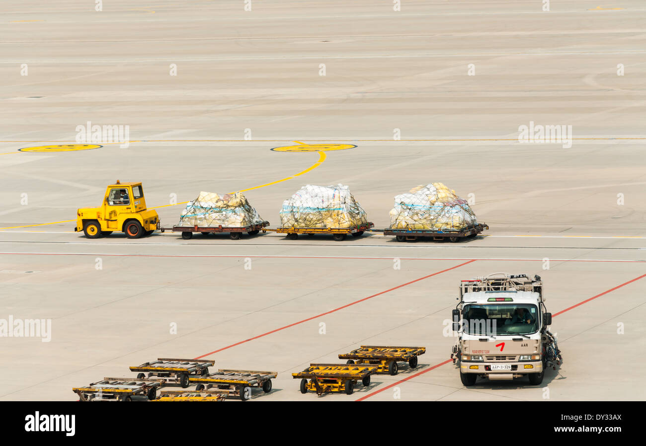 A baggage carrier hauling luggage to the terminal. - Stock Image