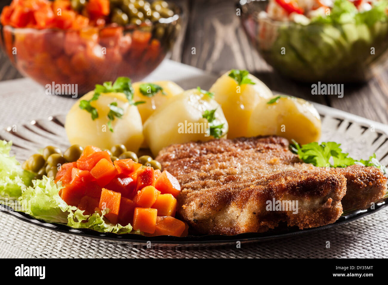 Breaded cutlet and prepared potatoes - Stock Image