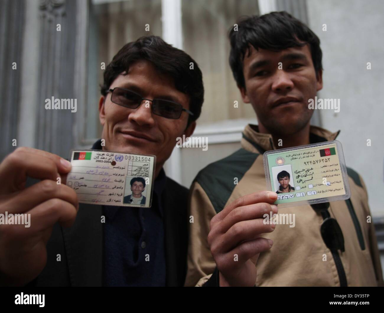 Kabul, Afghanistan. 5th Apr, 2014. Afghan men hold their identity cards while they wait at a polling center in Kabul, Afghanistan on April 5, 2014. Afghani presidential election takes place on Saturday. Credit:  Ahmad Massoud/Xinhua/Alamy Live News - Stock Image