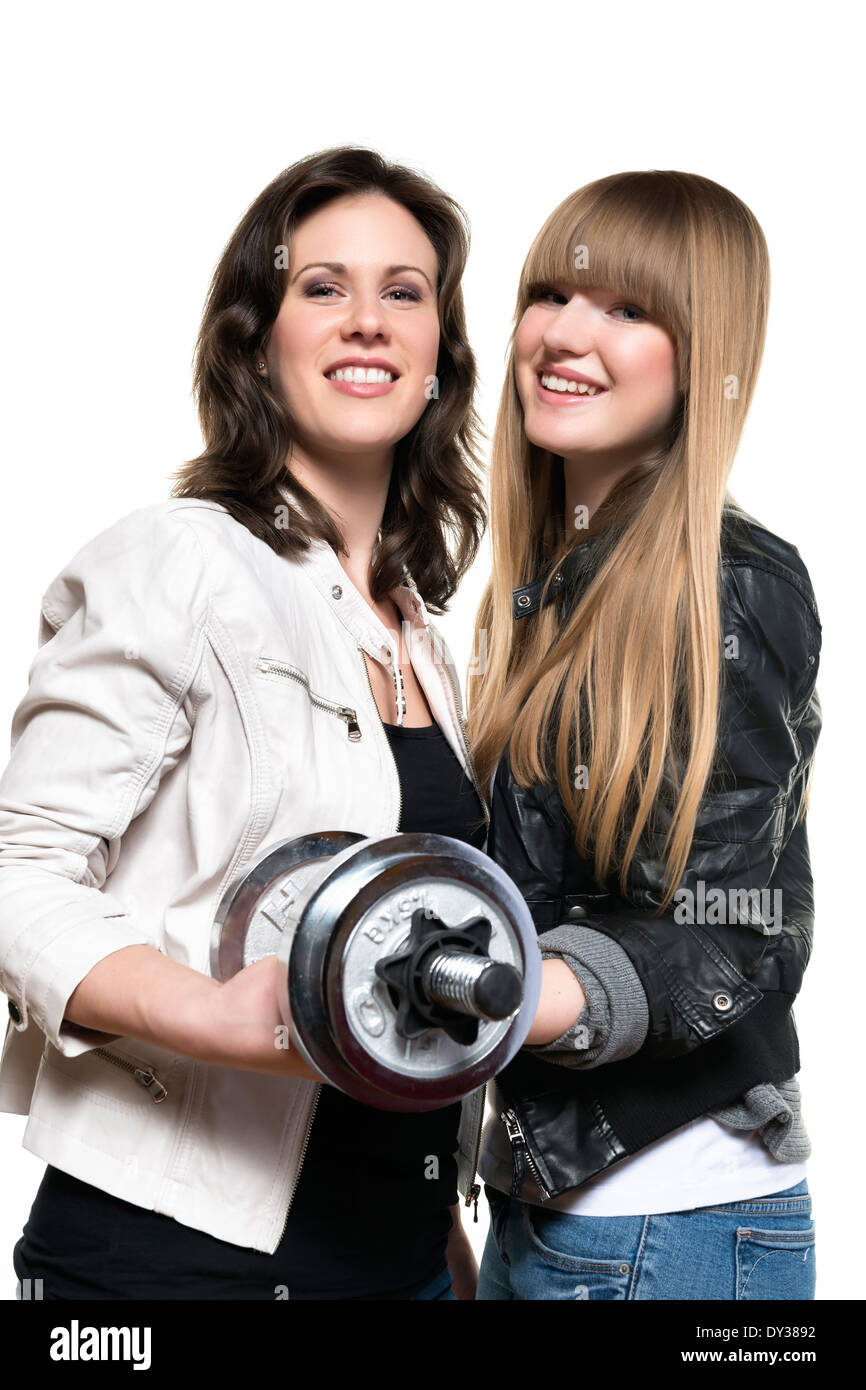 Two women blonde and brunette, with black and white leather jacket, holding together a silver dumbbell - Stock Image