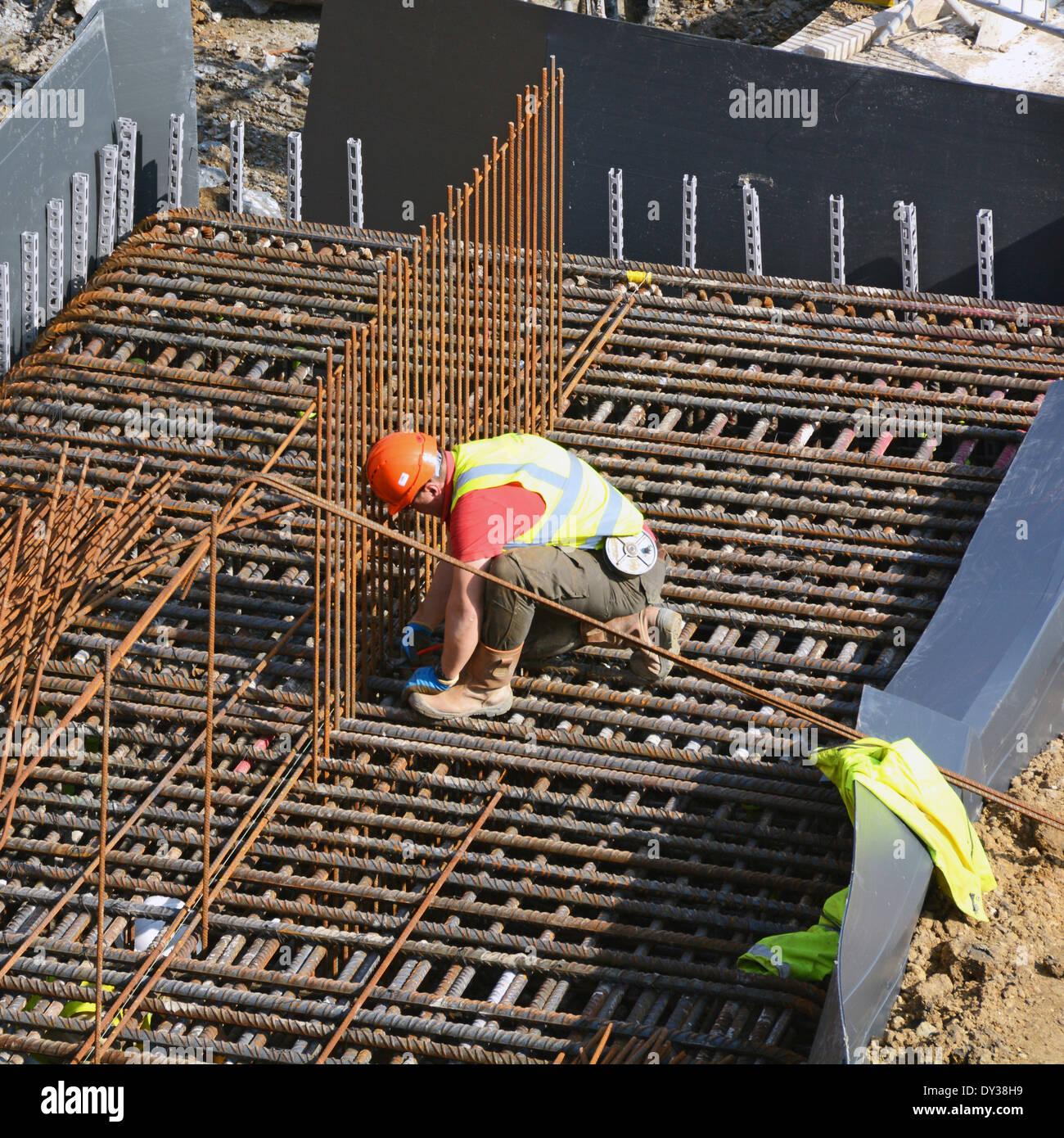 Construction site steelfixer tying steel reinforcement cage together as part of foundations for new building London England UK - Stock Image