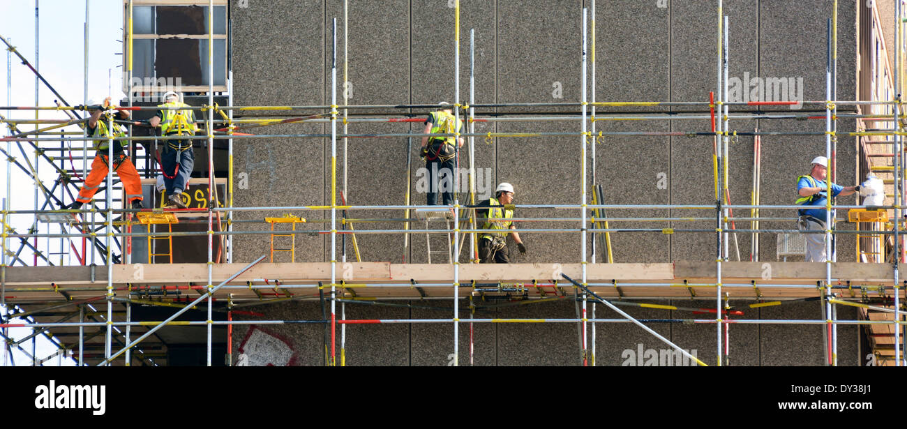 Workmen erecting scaffolding around obsolete social housing block prior to demolition - Stock Image