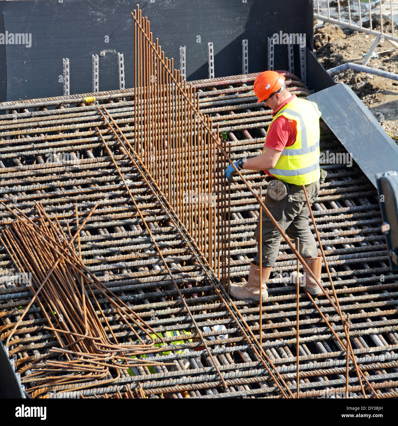 Steelfixer tying steel reinforcement cage together as part of foundations for new building - Stock Image