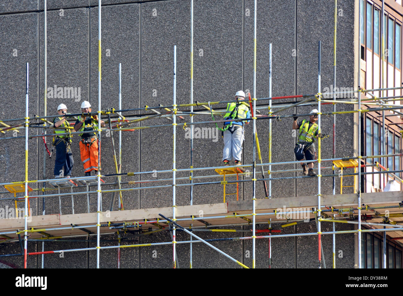 Workmen erecting scaffolding around obsolete social housing block prior to demolition for re development Heygate Estate Southwark South London England - Stock Image