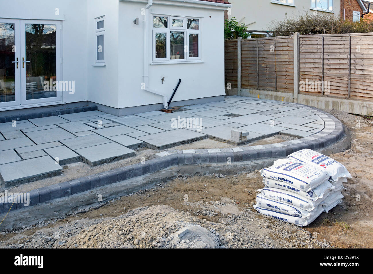 Paving slabs being laid as a patio to back garden of detached house after completion of rear extension Stock Photo