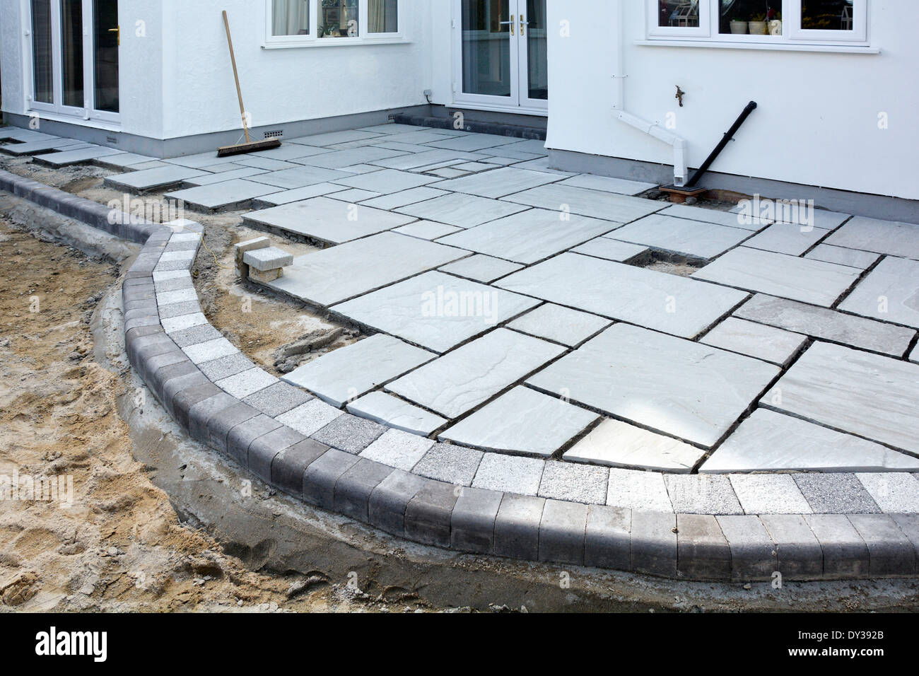 patio slabs. Paving Slabs Being Laid As A Patio To Back Garden Of Detached House After Completion Rear Extension Essex England UK