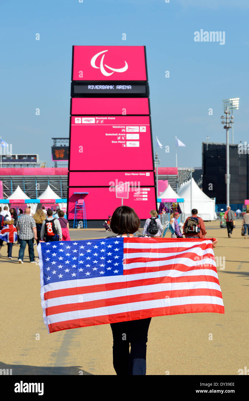 Woman draping stars and stripes American flag over her shoulders near the Riverside Arena in London 2012 Olympic Park Paralympics games England UK - Stock Image