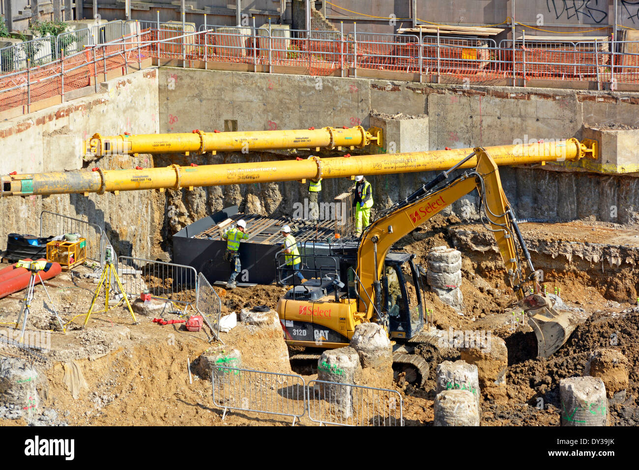 Diagonal shoring struts in pace across corners of retaining walls on large construction site with men working below - Stock Image