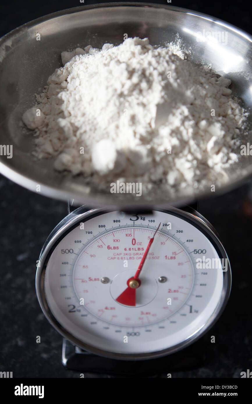 Weighing scales measuring out 150g of flour - Stock Image