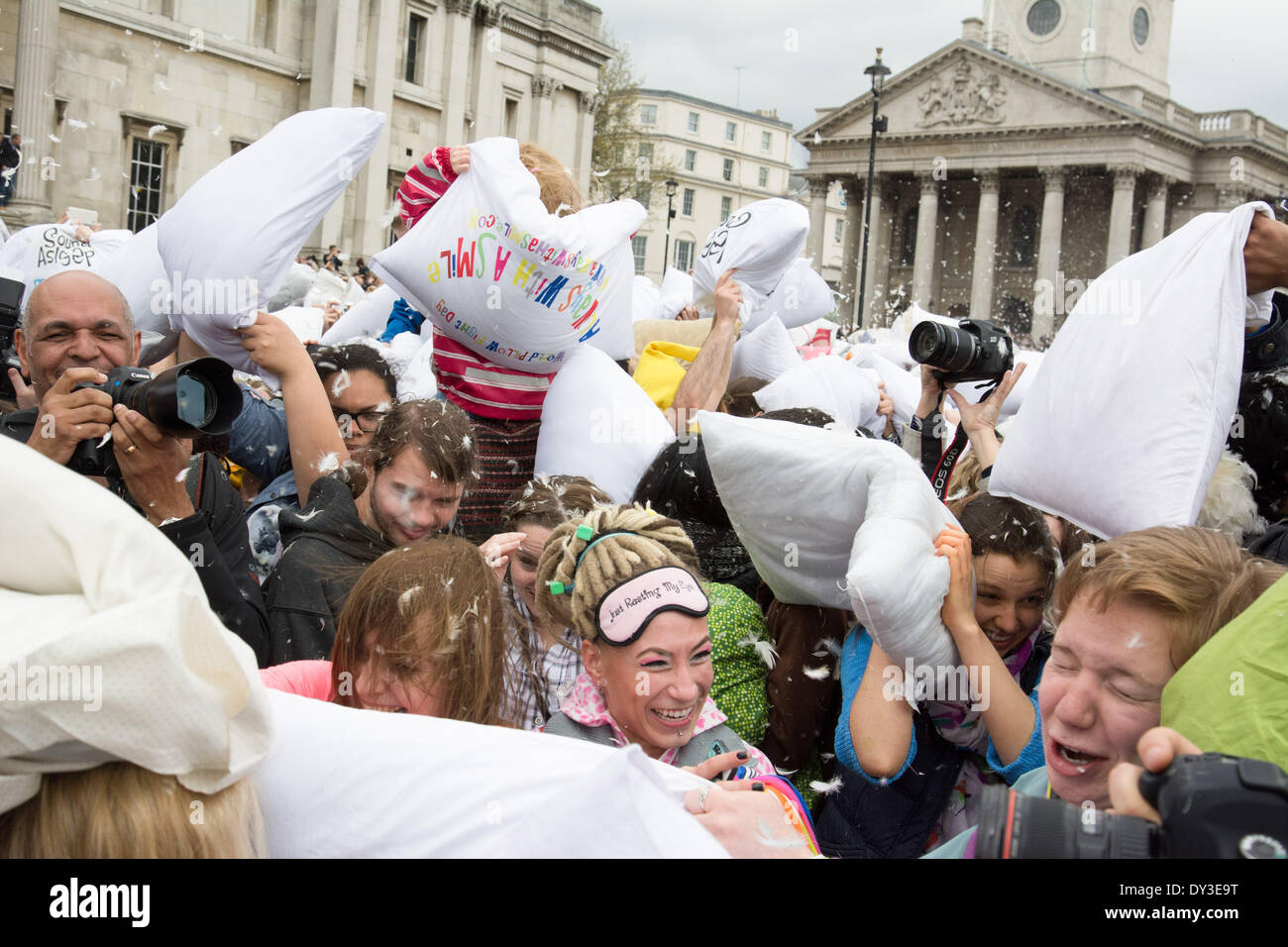 A laughing, grimacing crowd wield their pillows during international Pillow Fight Day, an annual flashmob in which people all over the world gather together to make the feathers fly. Credit:  Patricia Phillips/Alamy Live News - Stock Image