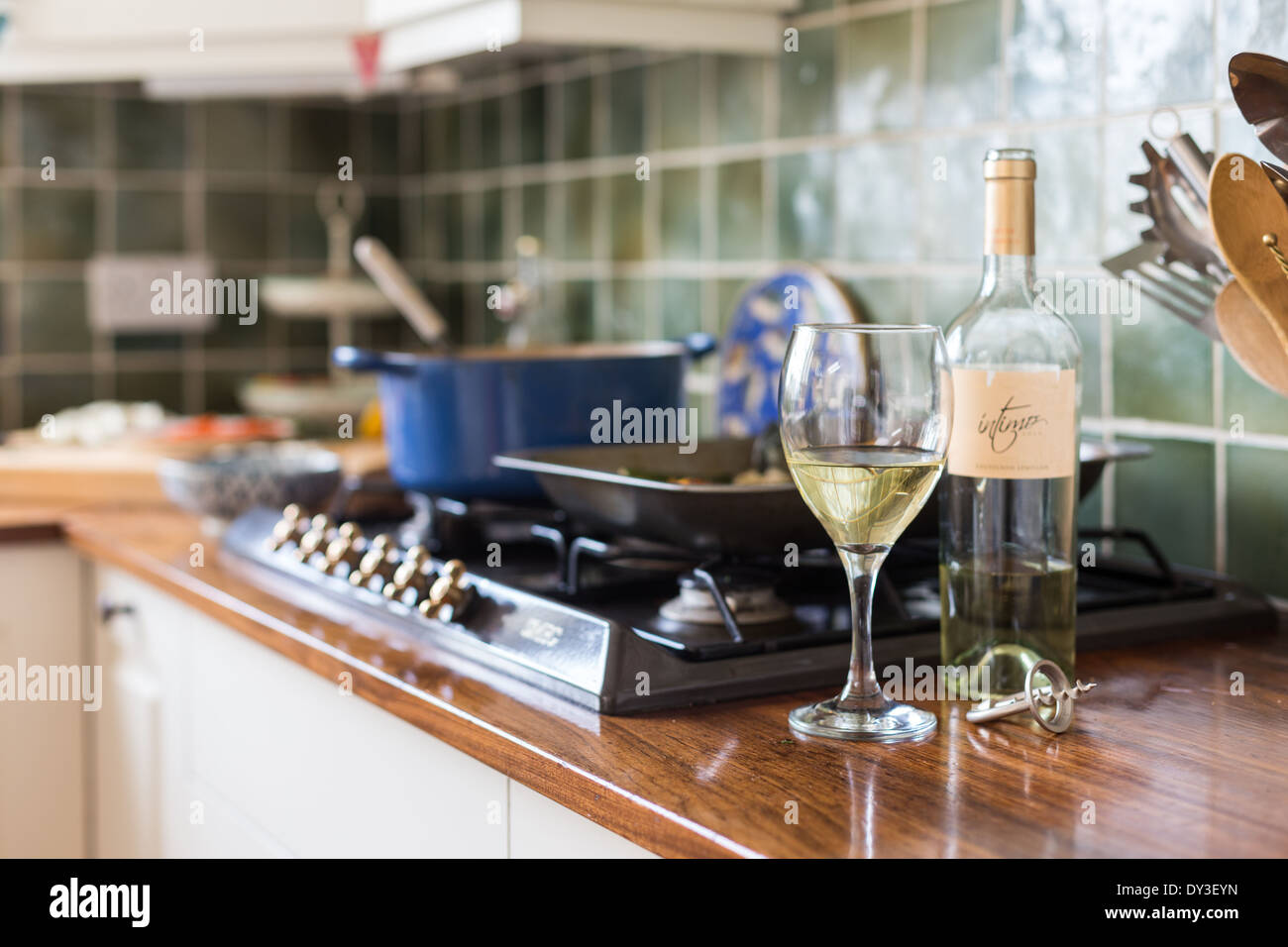 glass of wine with bottle by cooker - Stock Image