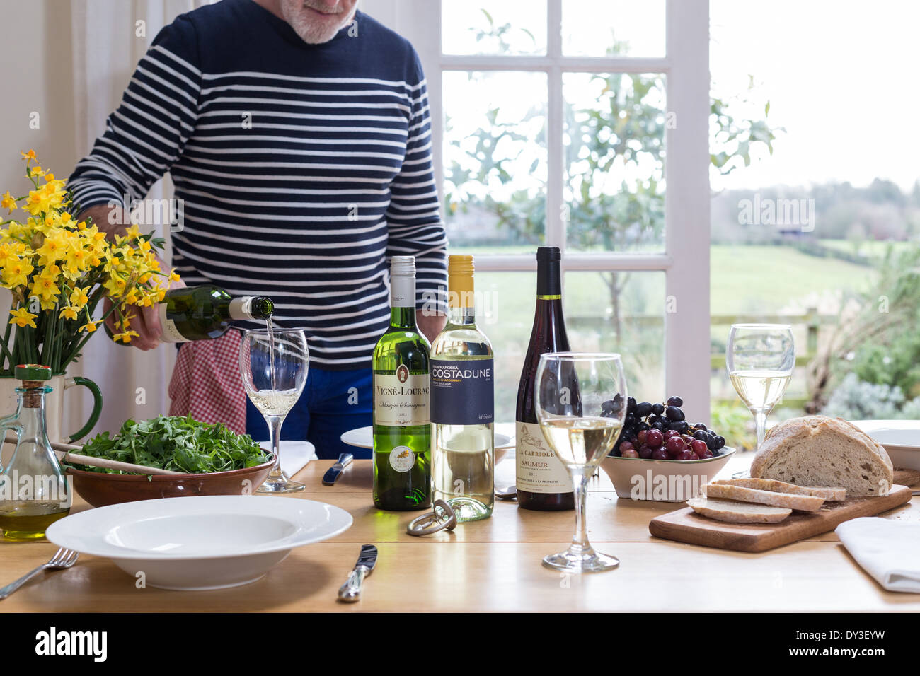 man pours wine at lunch time tasting session - Stock Image