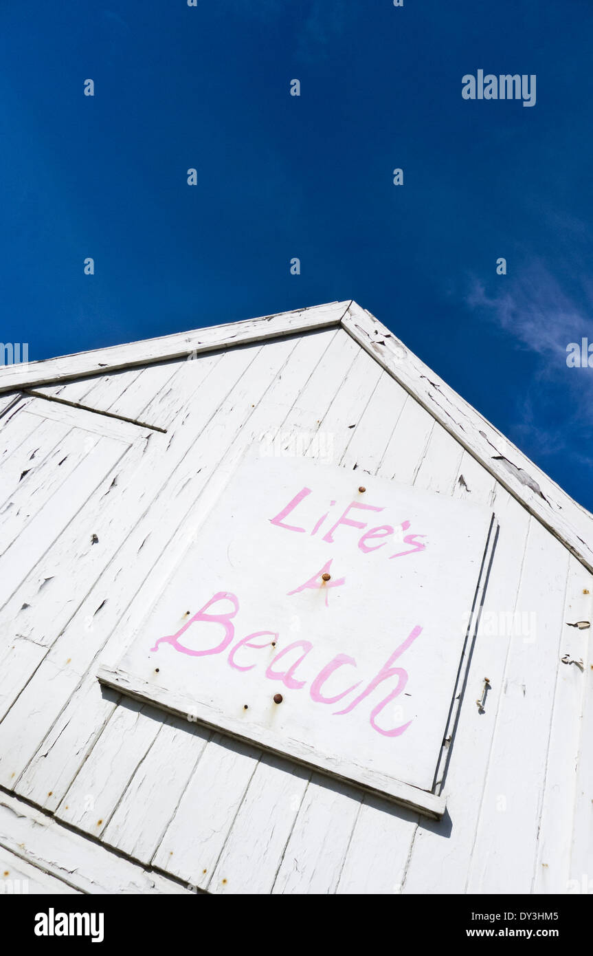 'LiFe's A Beach' painted sign on a white beach hut. - Stock Image