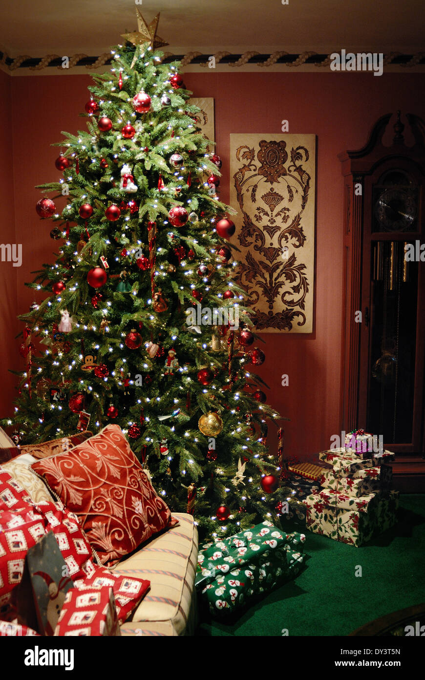 A Christmas tree is beautifully decorated and surrounded by Christmas gifts.. - Stock Image