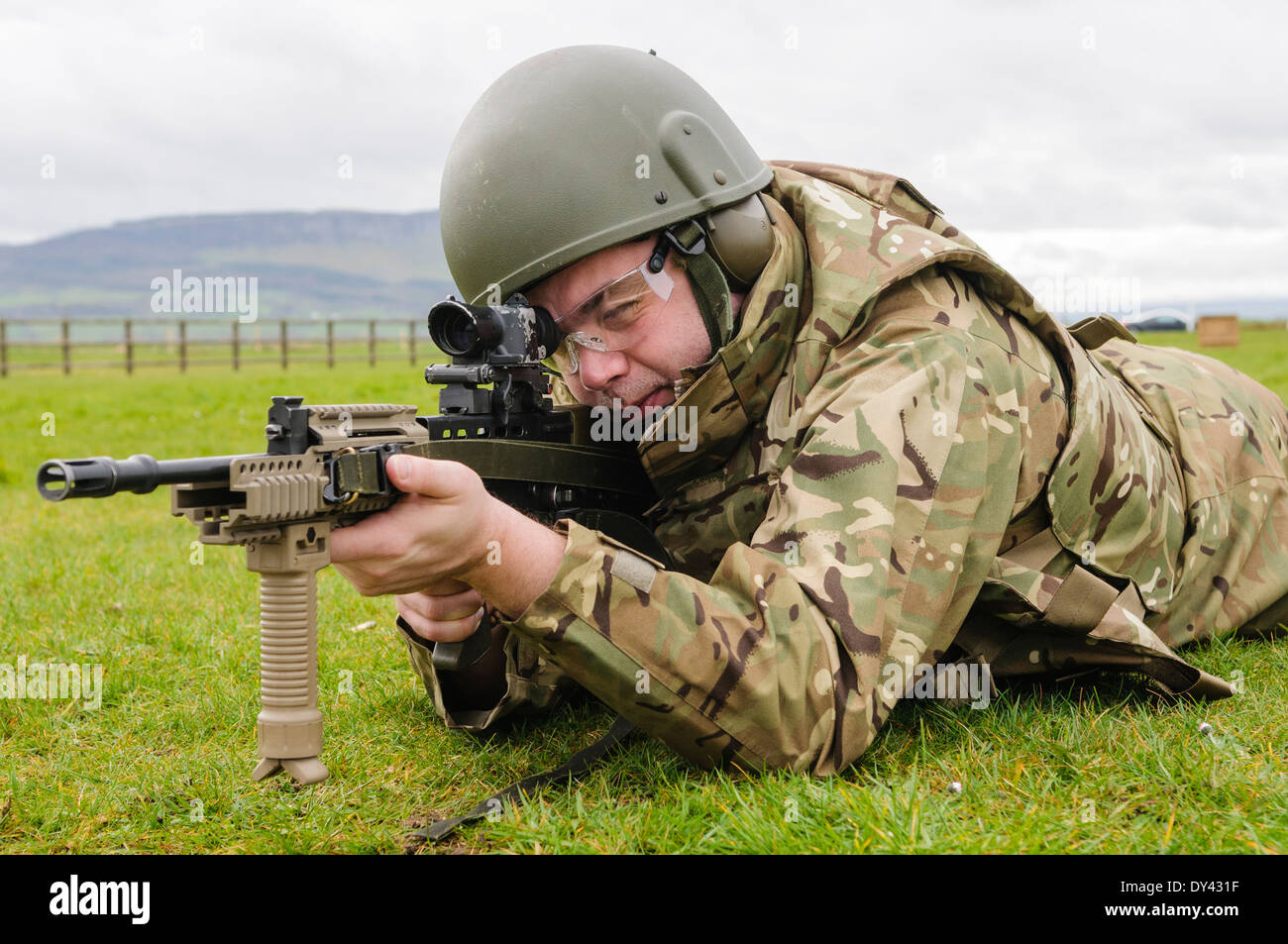 A British Army soldier lies prone on a firing range with a SA80 L85A2 assault rifle - Stock Image