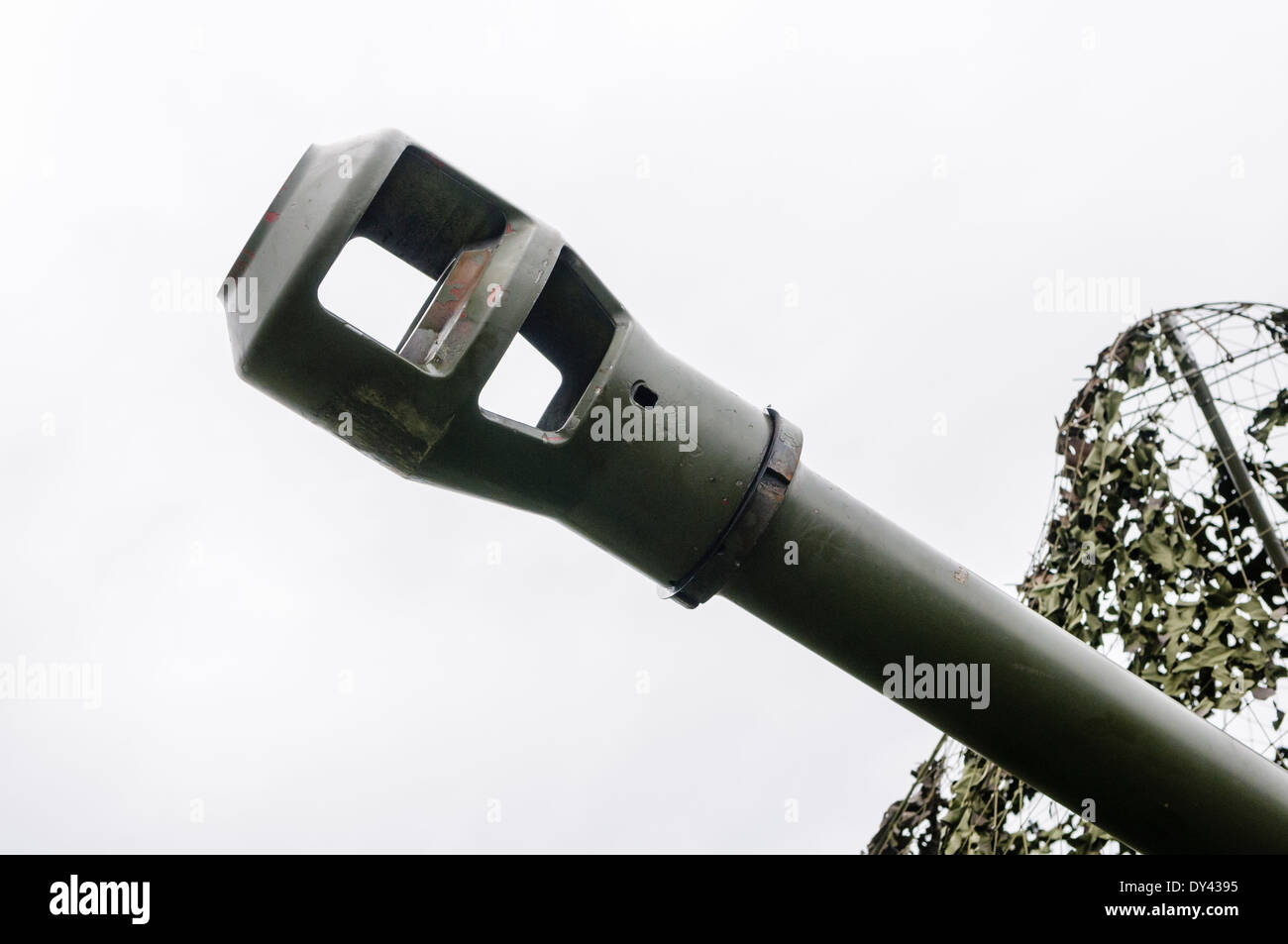 Muzzle of a 105mm Light Artillery Gun pokes through camouflage netting in a field - Stock Image