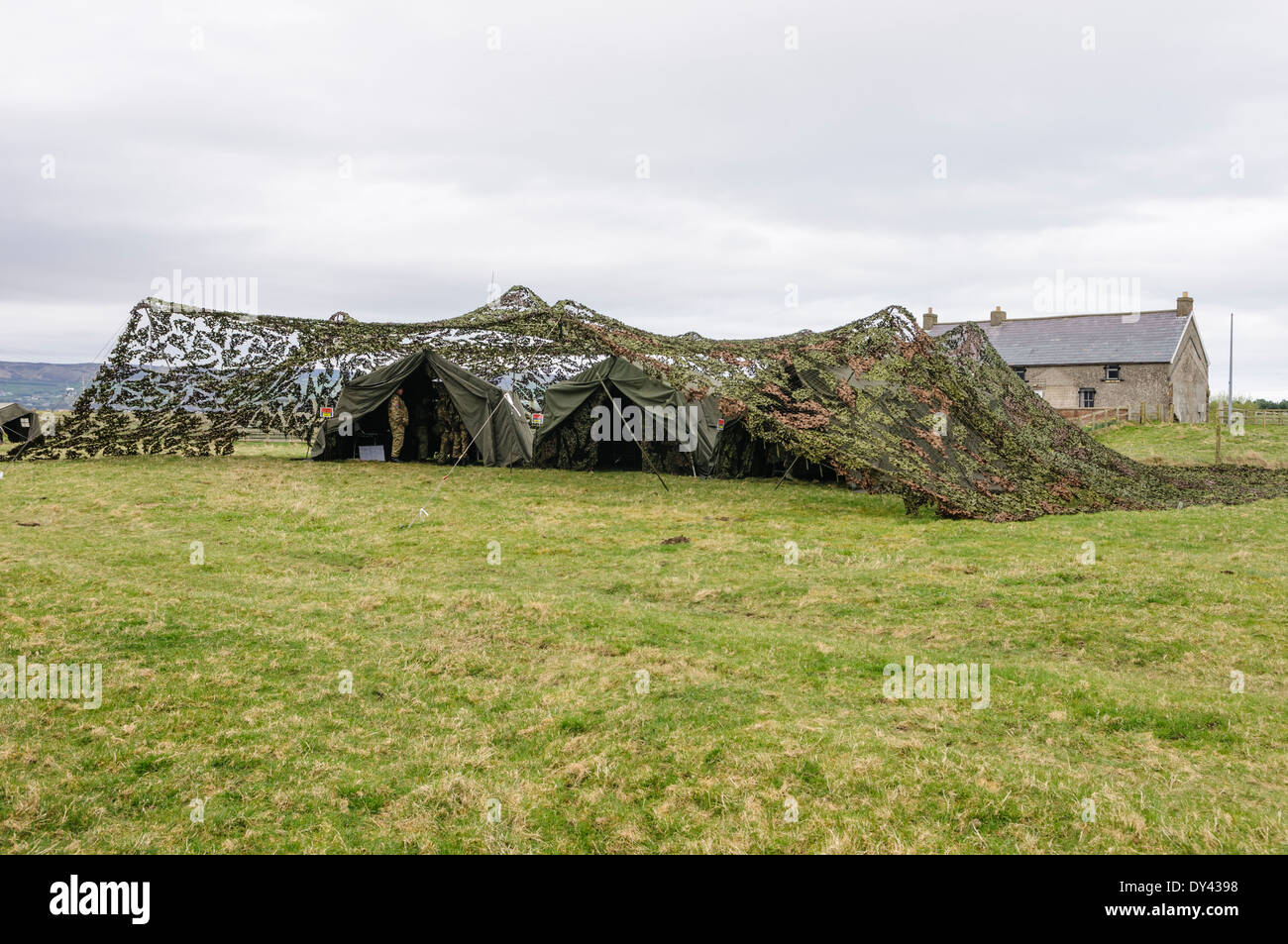 Tents belonging to a mobile command post are covered with camouflage netting in a field - Stock Image