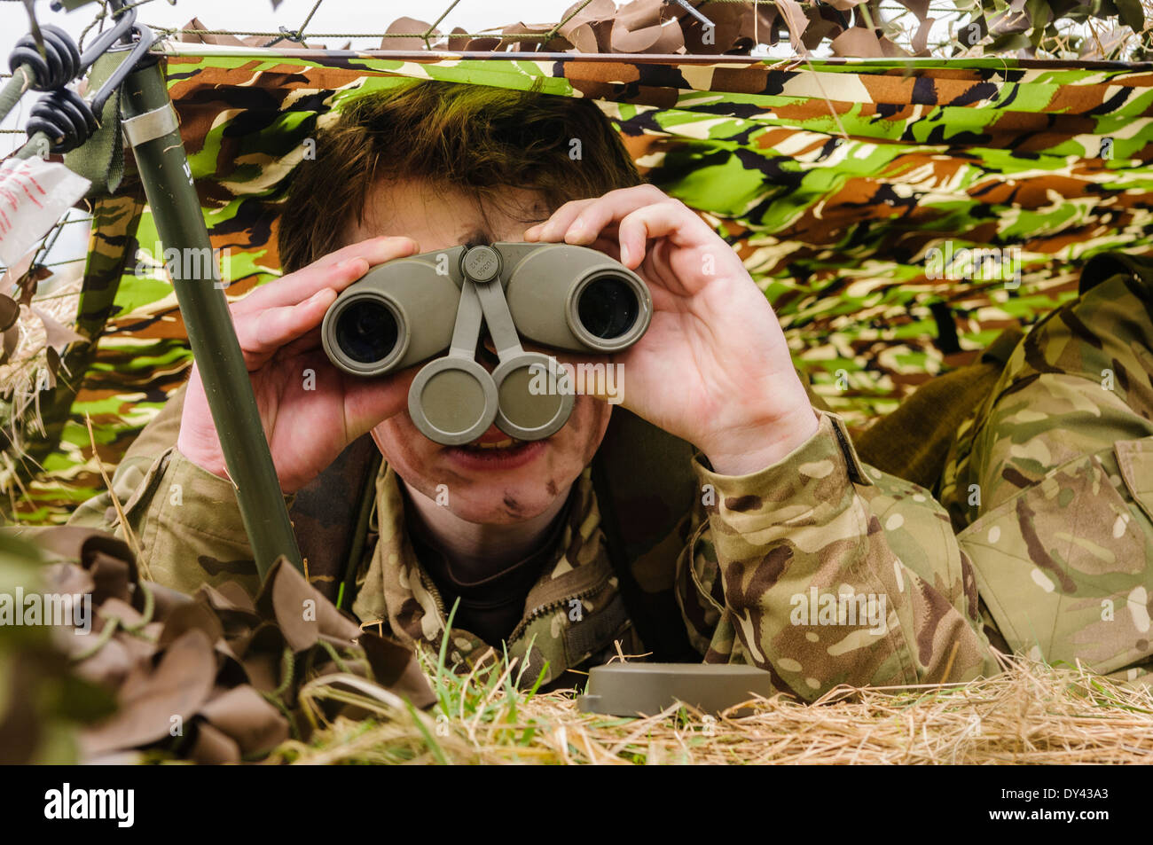 A soldier looks through binoculars as she hides underneath camouflage netting in a forward observation post - Stock Image