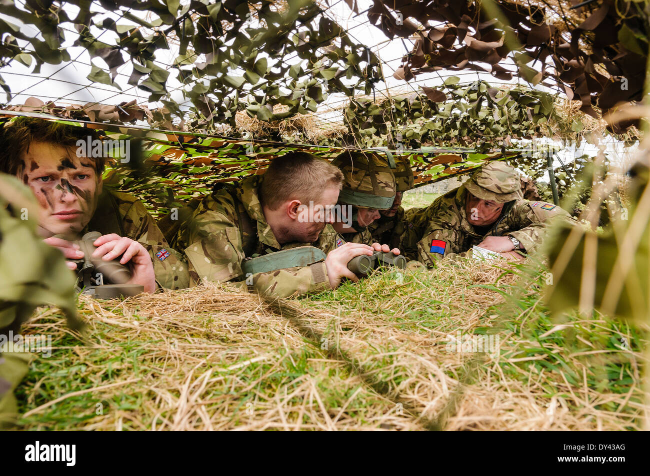 A senior officer gives instructions to soldiers as they hide underneath camouflage netting in a forward observation post - Stock Image