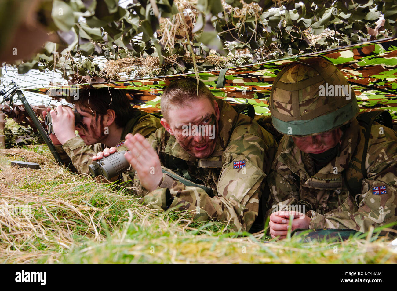 Three soldiers hide underneath camouflage netting in a forward observation post - Stock Image