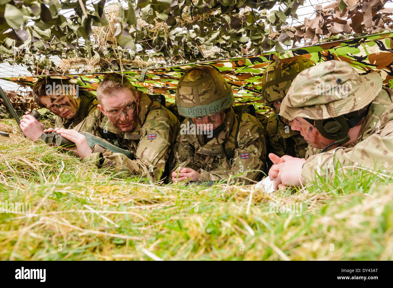 A senior officer gives instructions to four soldiers as they hide underneath camouflage netting in a forward observation post - Stock Image