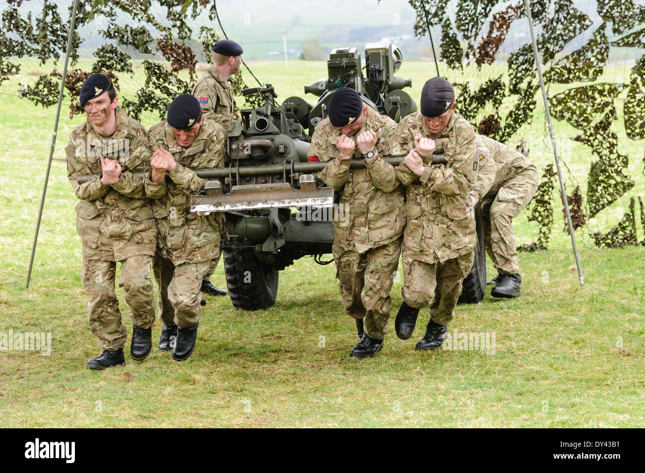 Soldiers from the Royal Artillery strain to pull a 105mm Light Artillery Gun - Stock Image