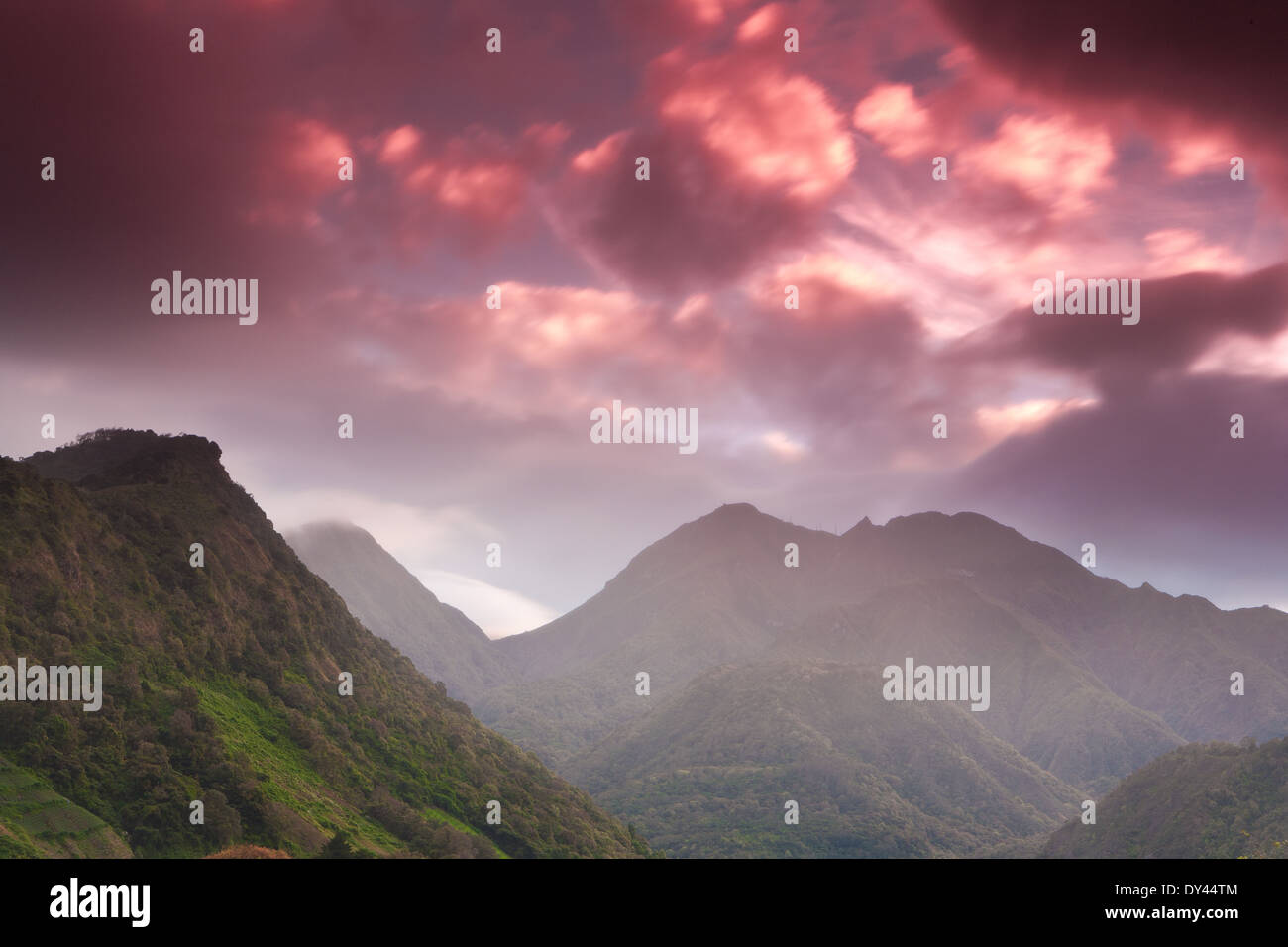 Colorful skies at sunrise and rainfall over Volcan Baru, 3475 m, in the Volcan Baru national park, Chiriqui province, Republic of Panama. - Stock Image
