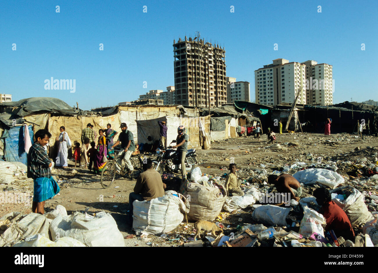 India Mumbai, slum and waste picker in Malad, background new apartment building, collecting plastic garbage for Stock Photo