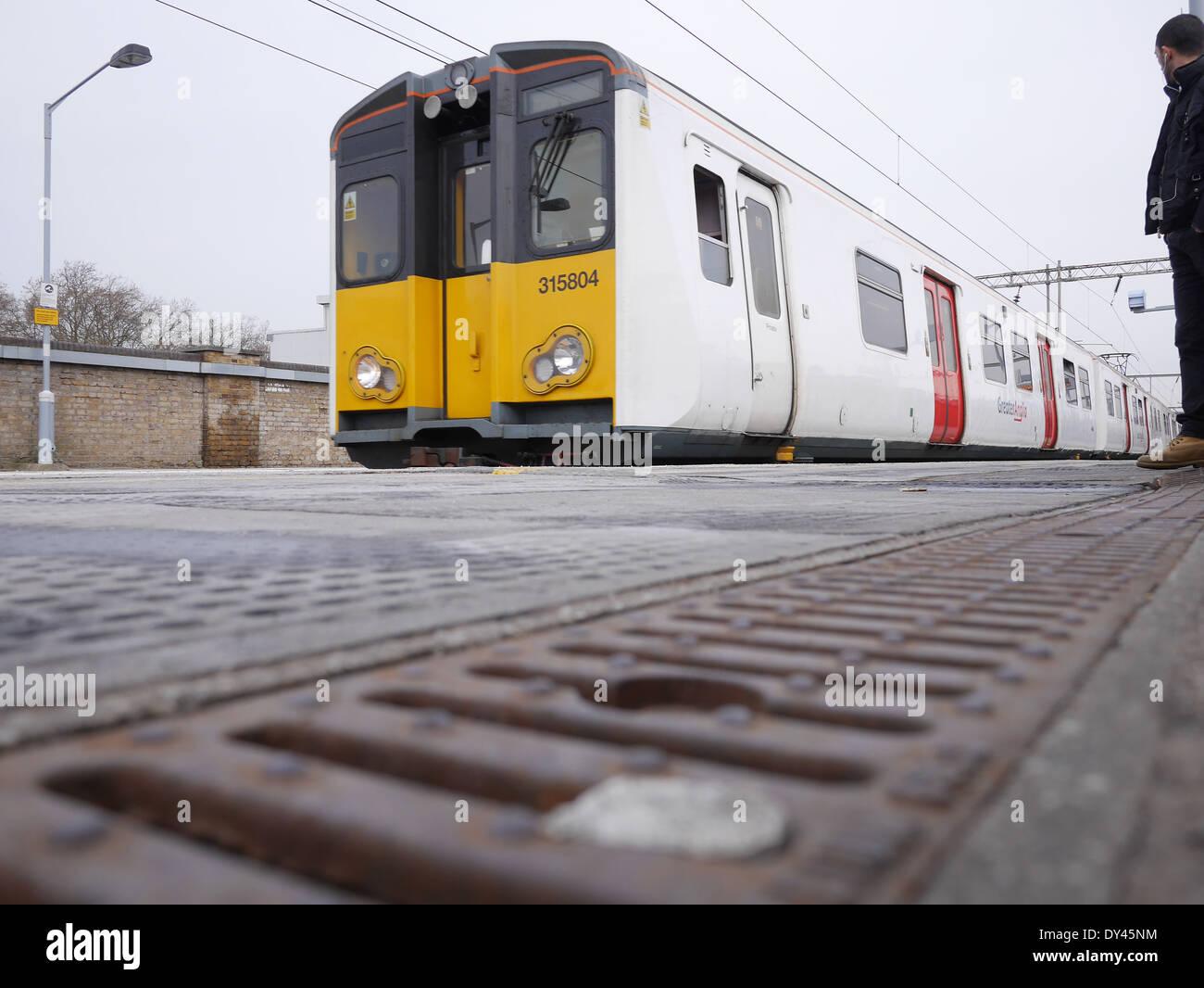 Overground train approaching rail station London Fields station London UK - Stock Image