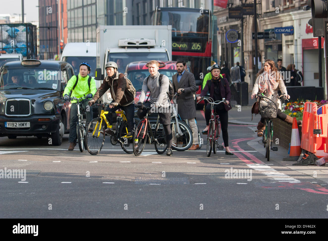 London cyclists mingle with traffic at stop lights during morning rush hour - Stock Image