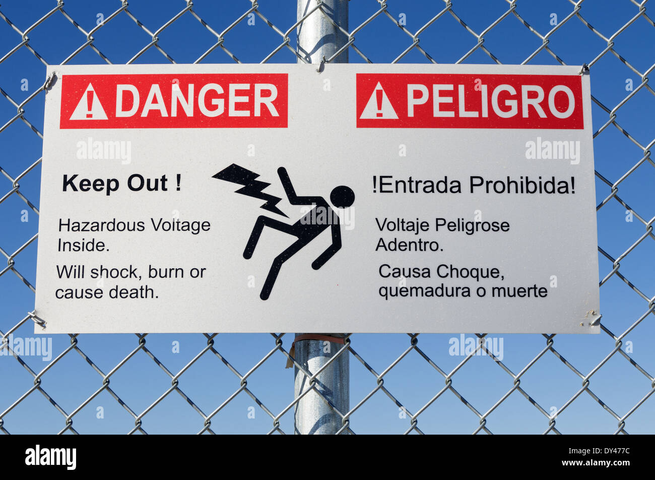 danger hazardous voltage keep out sign in English and Spanish on a fence with blue sky - Stock Image