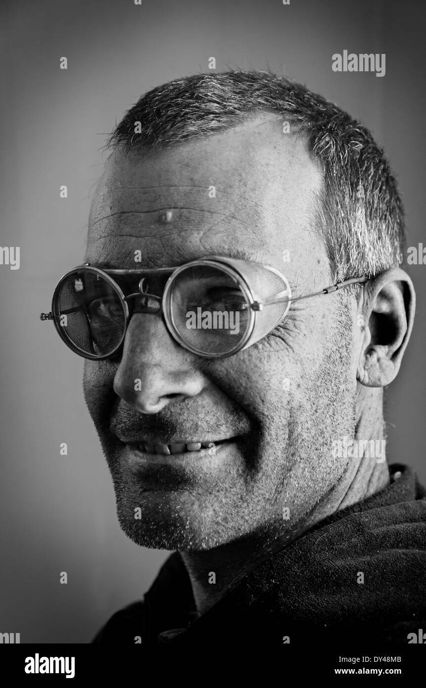 black and white image of man with steampunk style old safety glasses with mesh side shields - Stock Image
