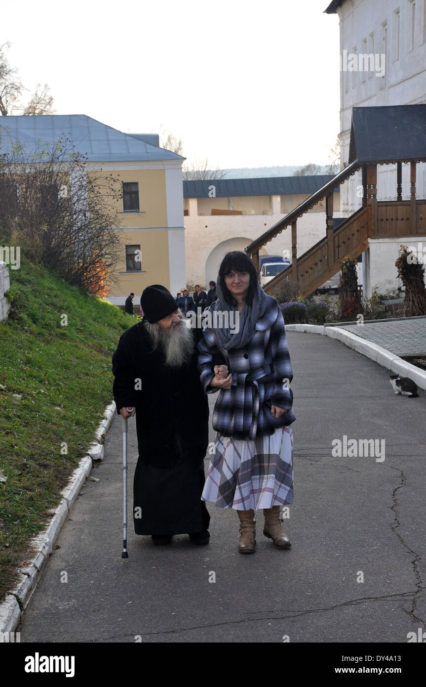 Old Russian Orthodox priest with young female helper at Savvino-Storozhevsky Monastery in Zvenigorod in Russia - Stock Image