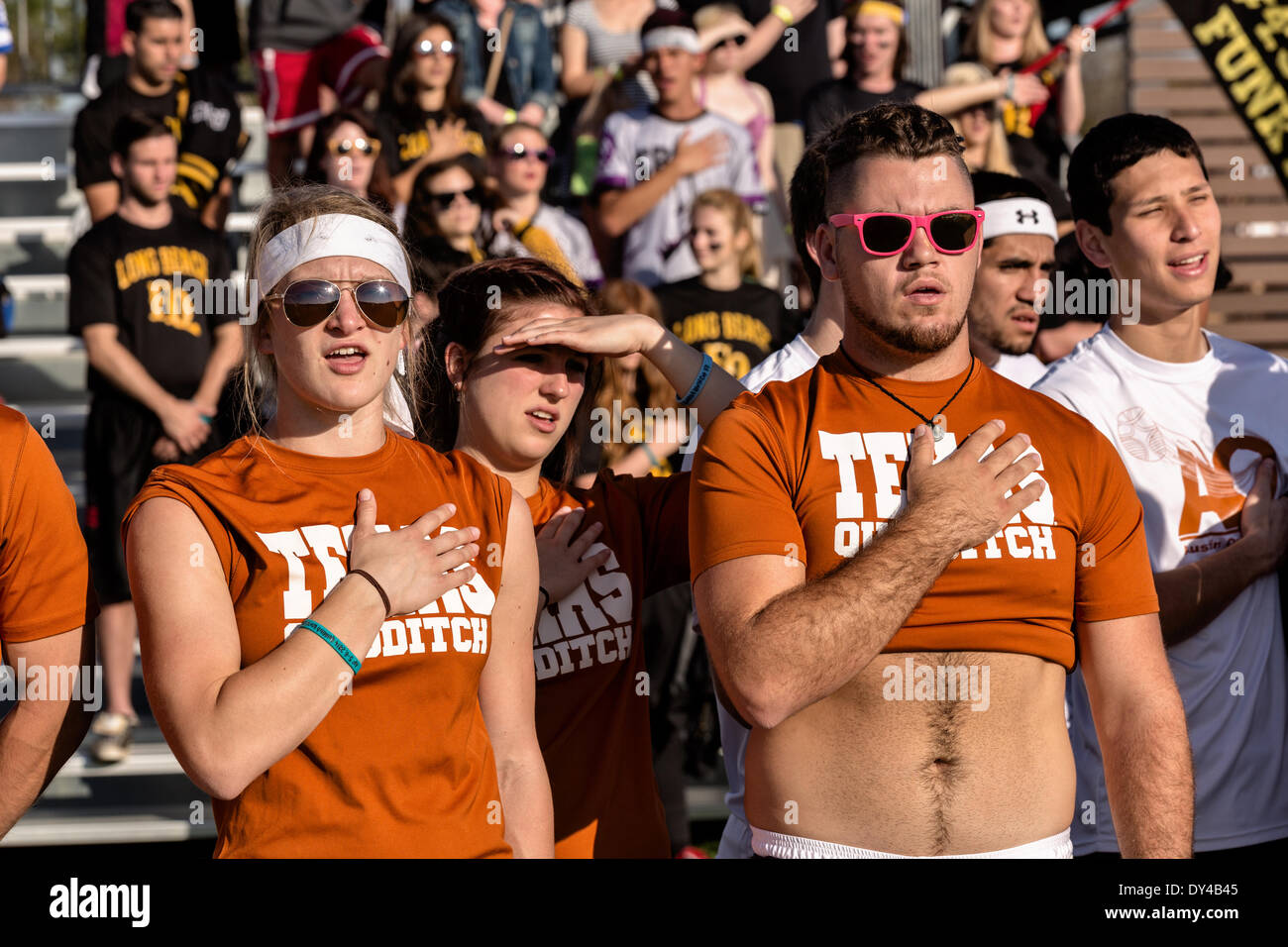 Members of the University of Texas team stand for the national anthem during the opening ceremonies for the 7th Annual Quidditch World Cup April 5, 2014 in Myrtle Beach, South Carolina. The sport, created from the Harry Potter novels is a co-ed contact sport with elements from rugby, basketball, and dodgeball. A quidditch team is made up of seven athletes who play with broomsticks between their legs at all times. - Stock Image