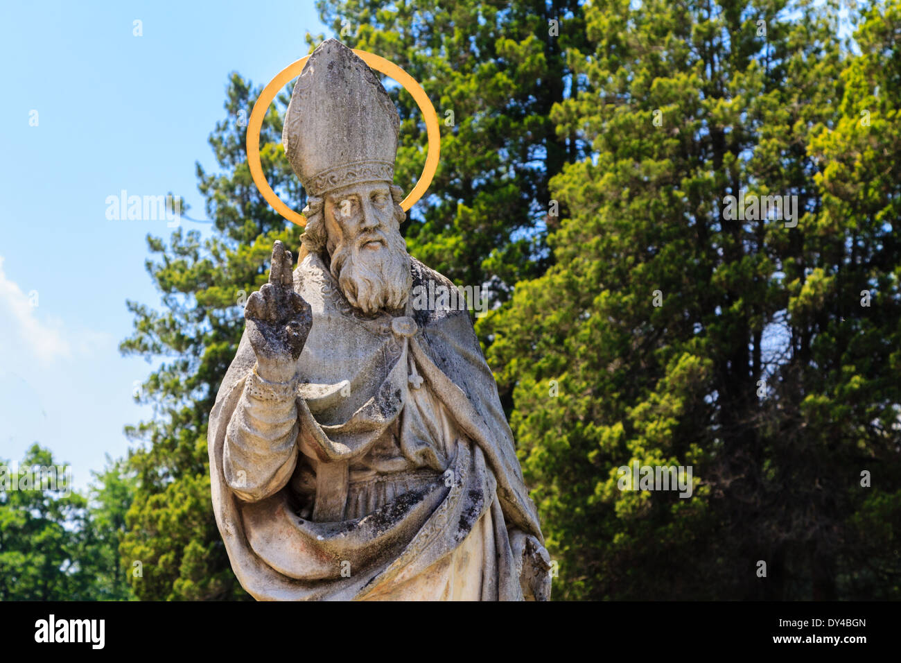 A stone statue of a saint outdoor with a bishop's hat and typical hand gesture - Stock Image