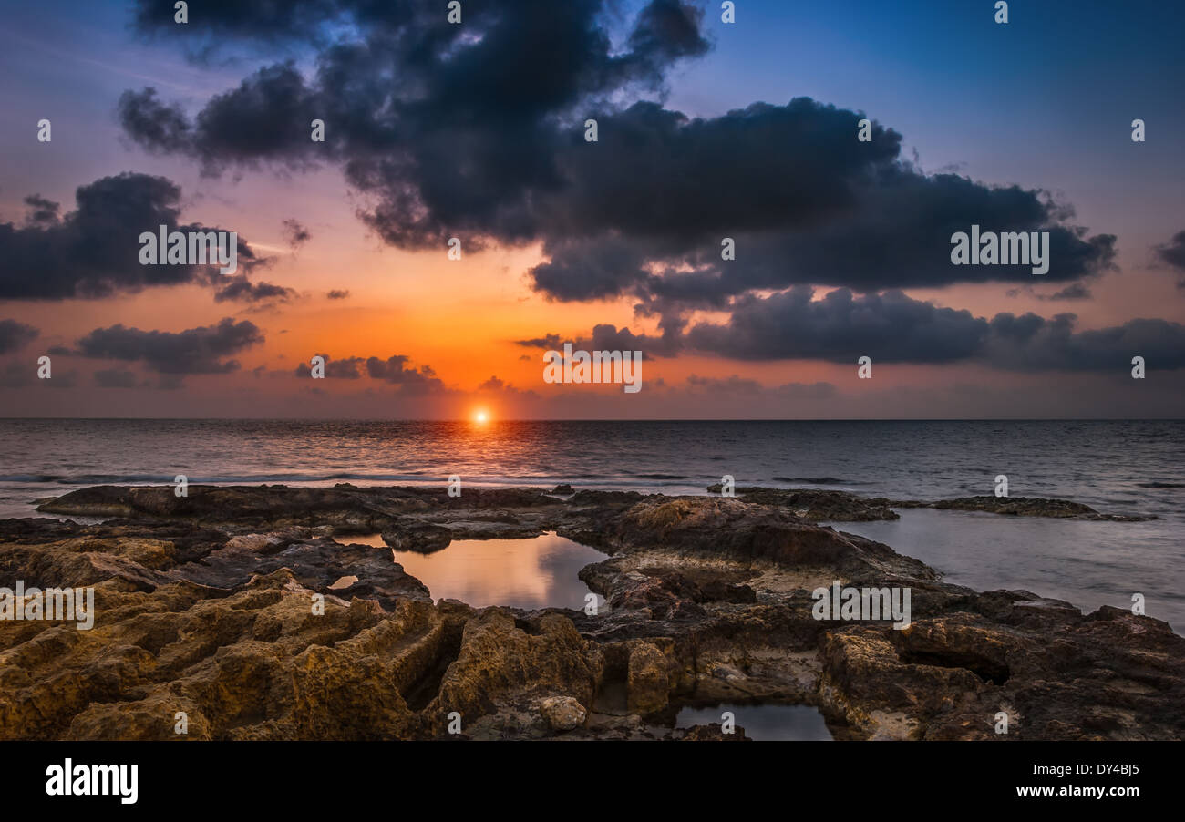Cloudy Sunset over the Sea and Rocky Beach - Stock Image
