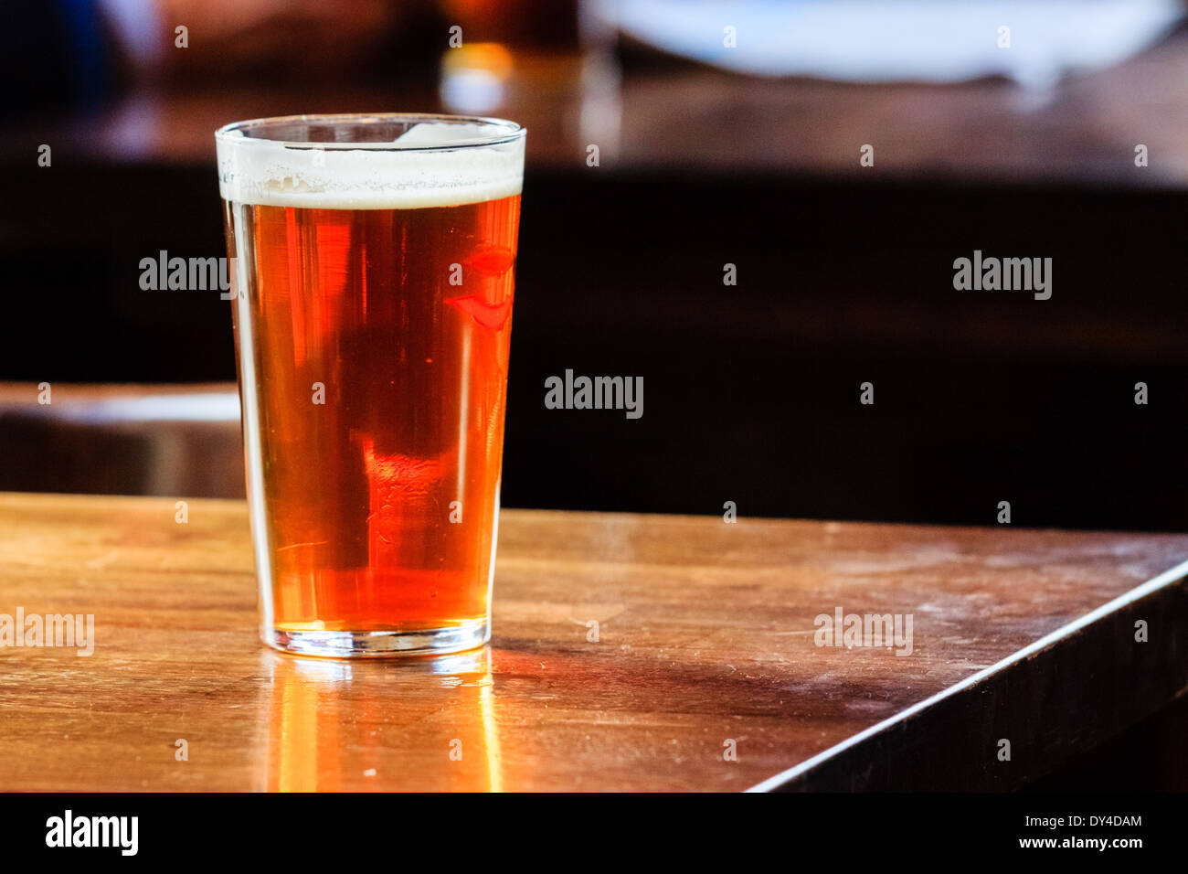An english ale on a wooden table in a pub in London, UK Stock Photo