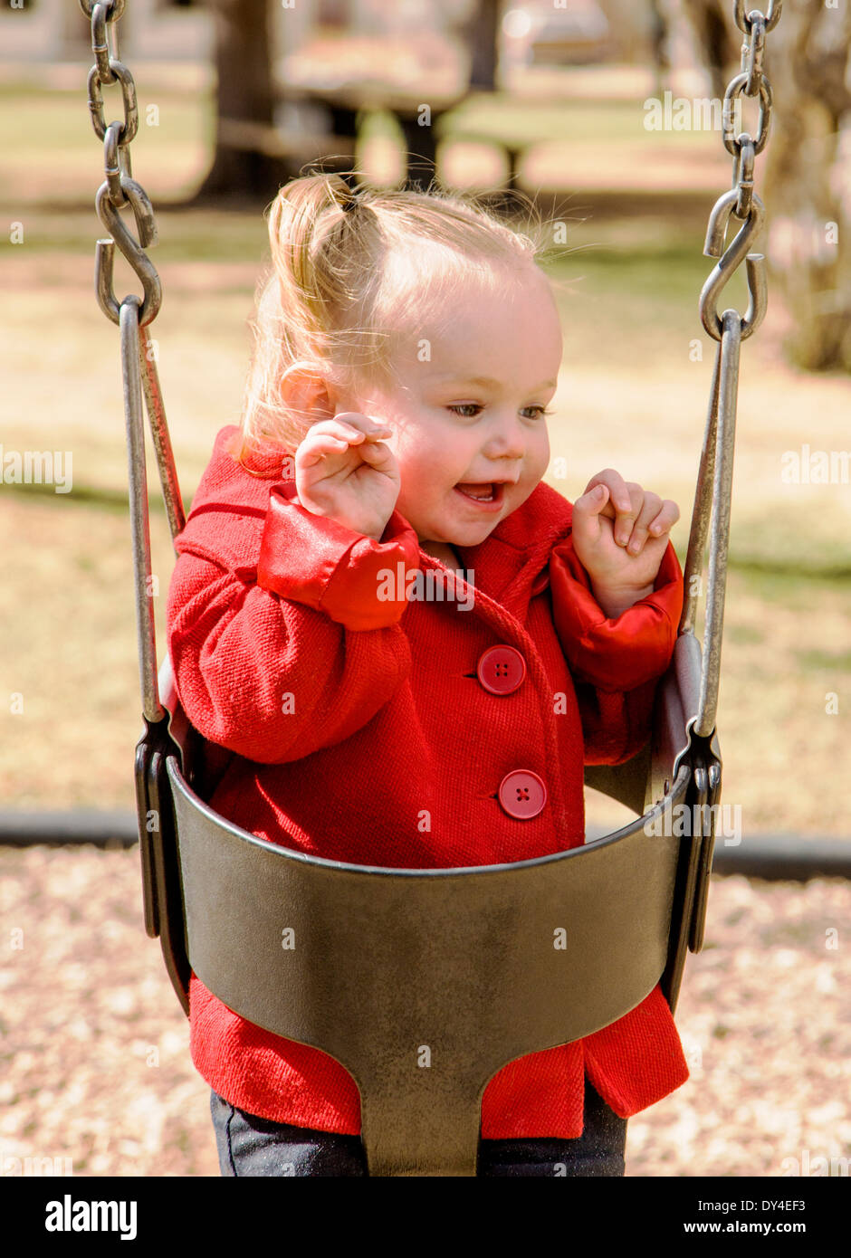Adorable, cute 16 month little girl swinging on a park playground - Stock Image