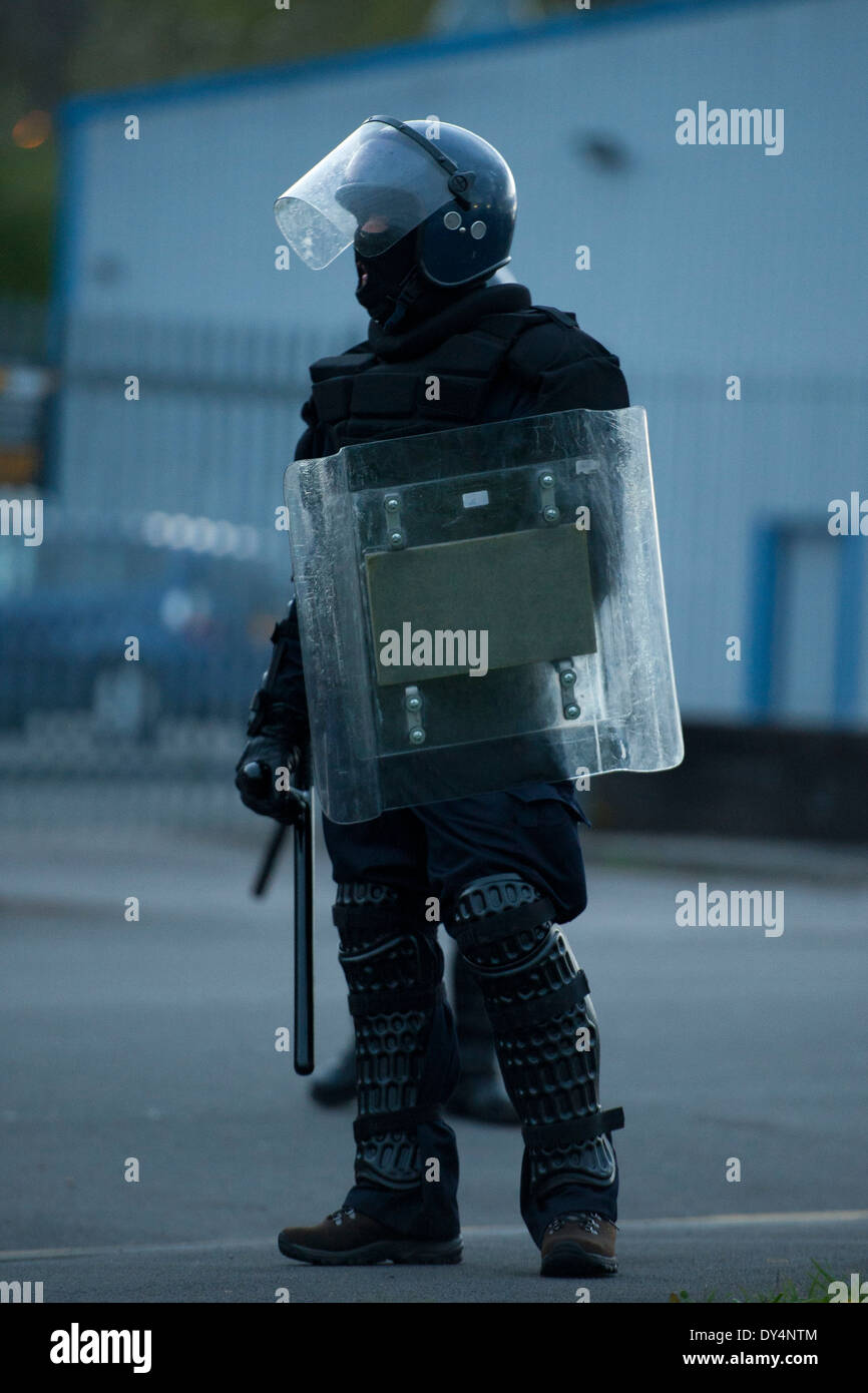 A riot police officer with shield, helmet and truncheon. - Stock Image