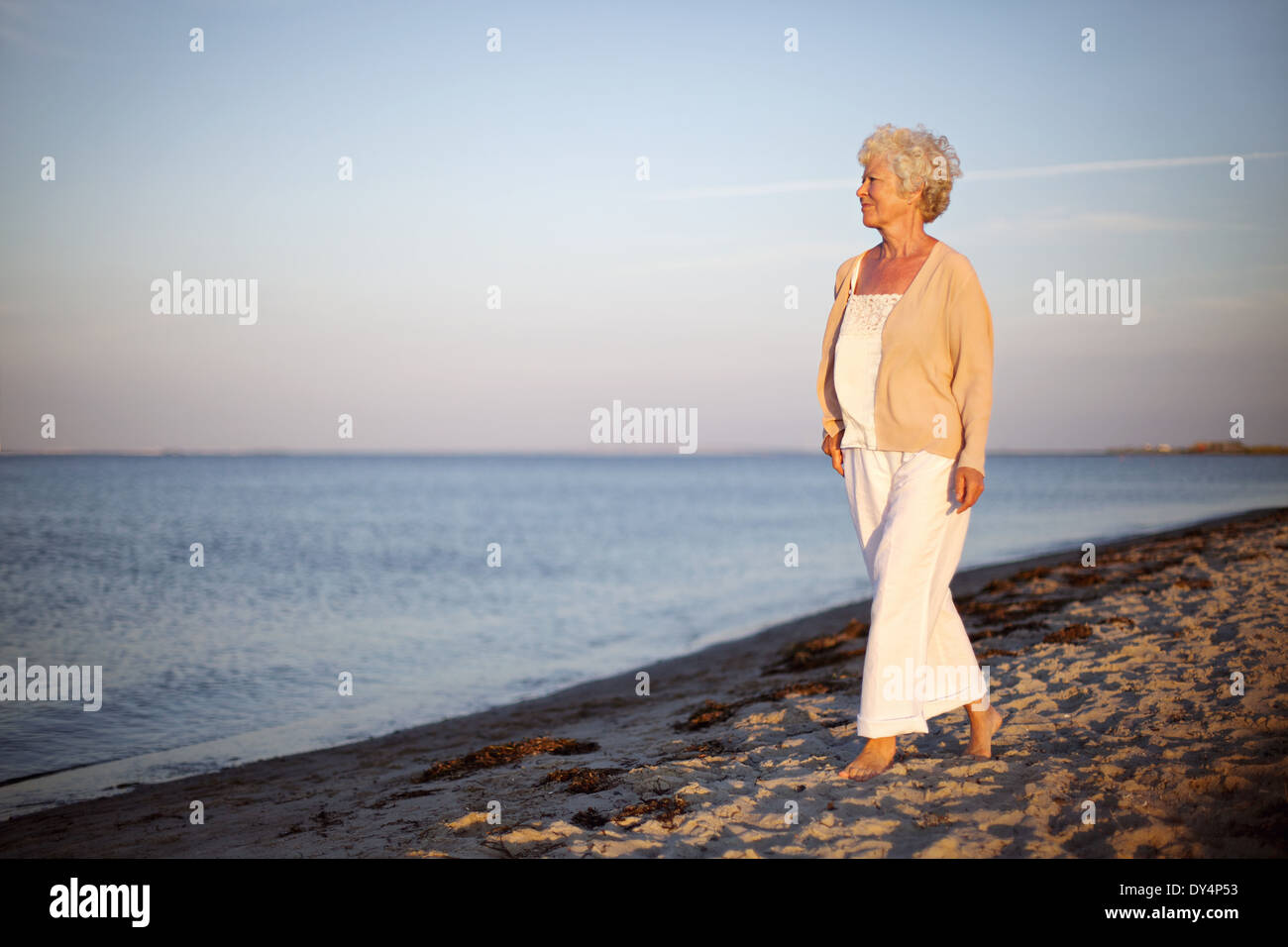 Portrait of a mature woman walking on the beach looking at the sea. Relaxed old lady strolling on the beach with copy space. - Stock Image