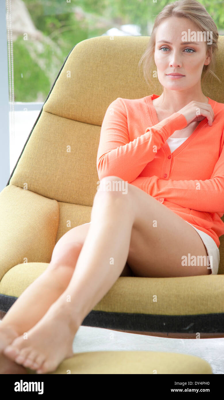 Young Woman Sitting on Armchair Stock Photo