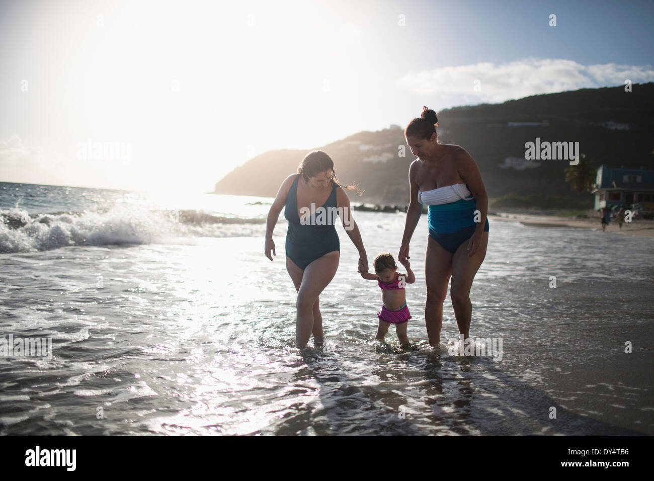 Toddler holding hands with mother and grandmother, walking in sea - Stock Image