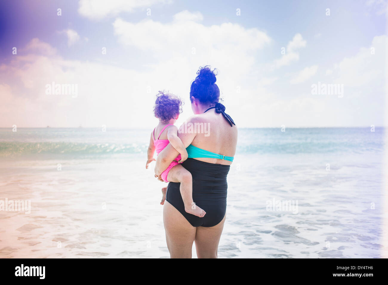 Rear view of mother and daughter looking out to sea - Stock Image