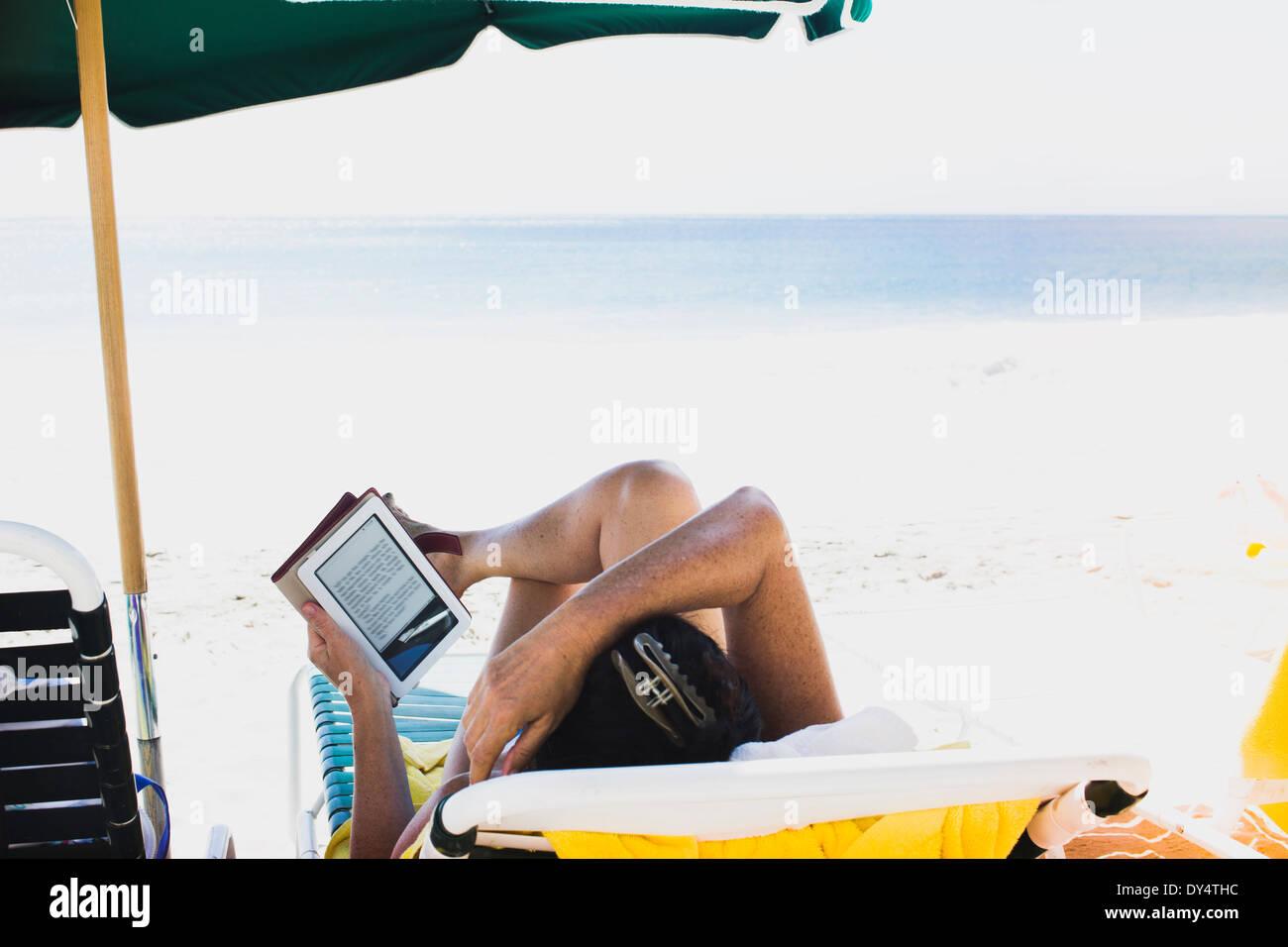 Woman lying on sun lounger, reading e-book - Stock Image