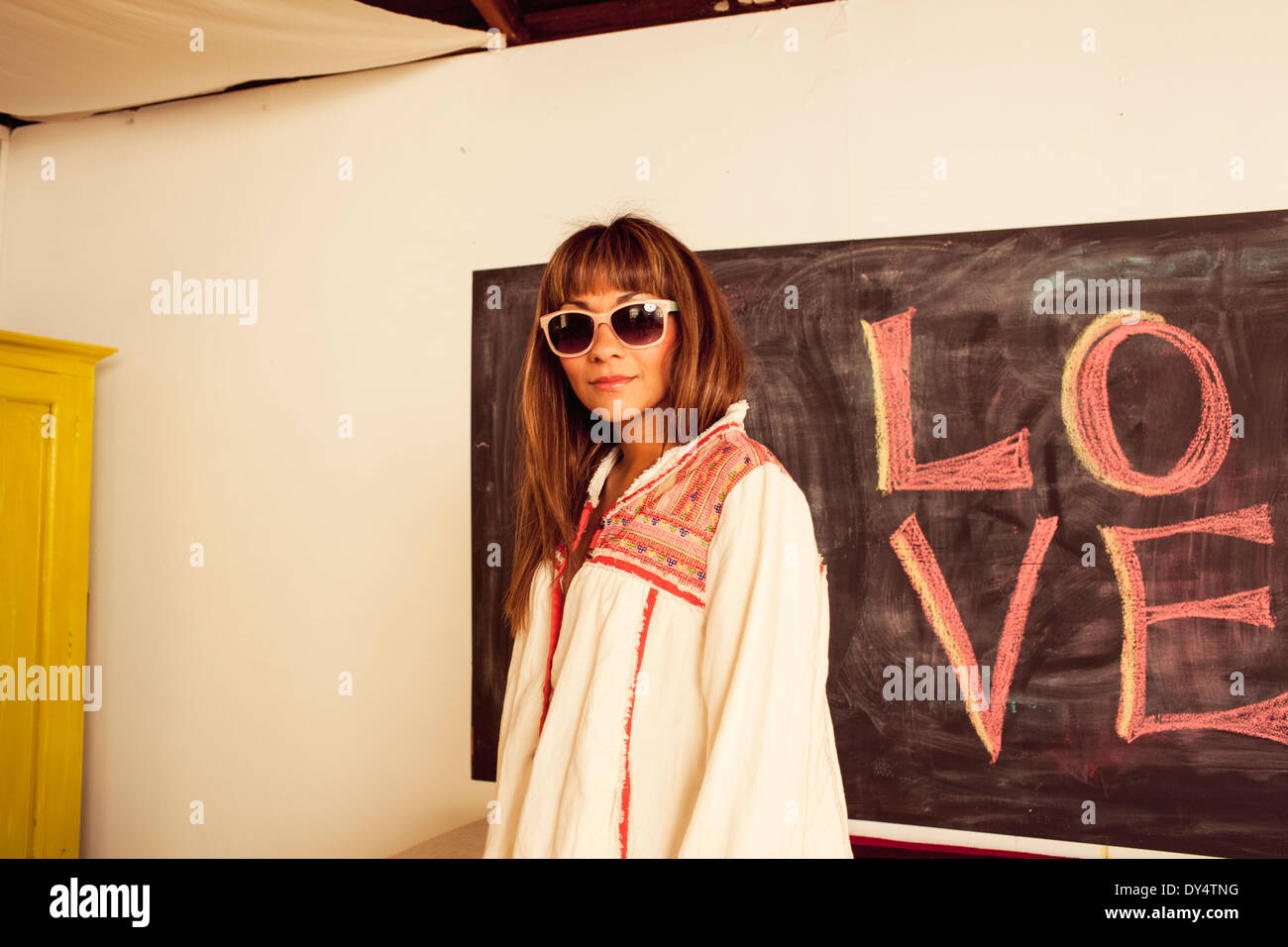 Woman wearing sunglasses, blackboard with word love - Stock Image