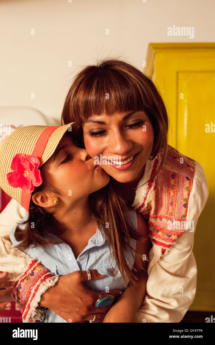 Daughter wearing straw hat kissing mother on cheek Stock Photo